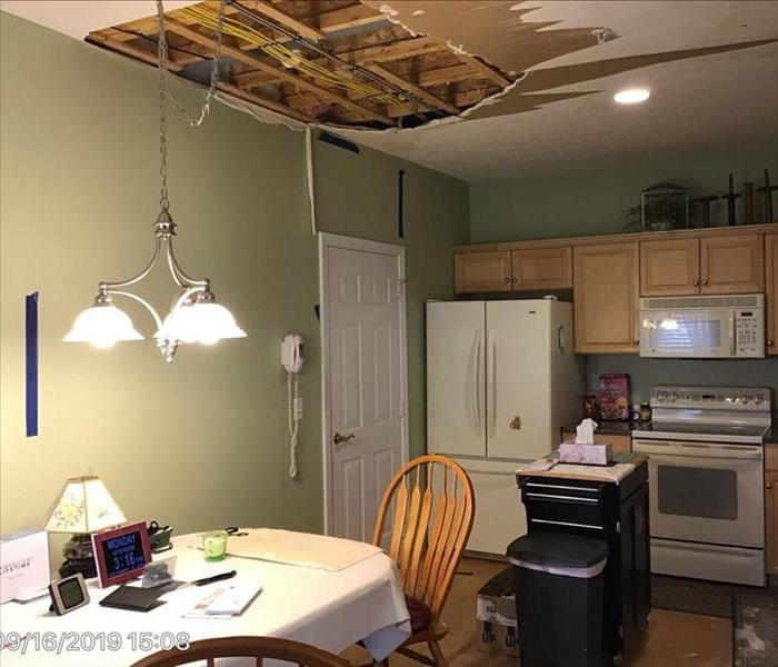 Water damaged kitchen with buckled hardwood floor, sagging ceiling, and wet drywall.