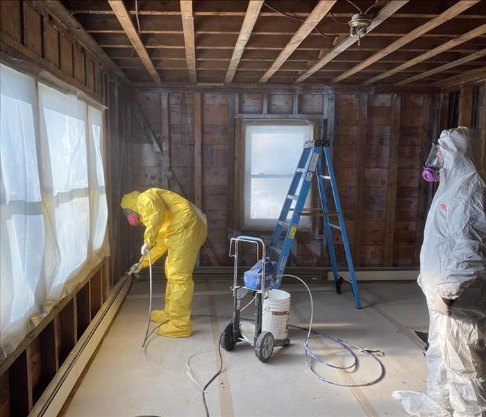 Technicians are applying smoke sealant to wood framing structure after the fire restoration