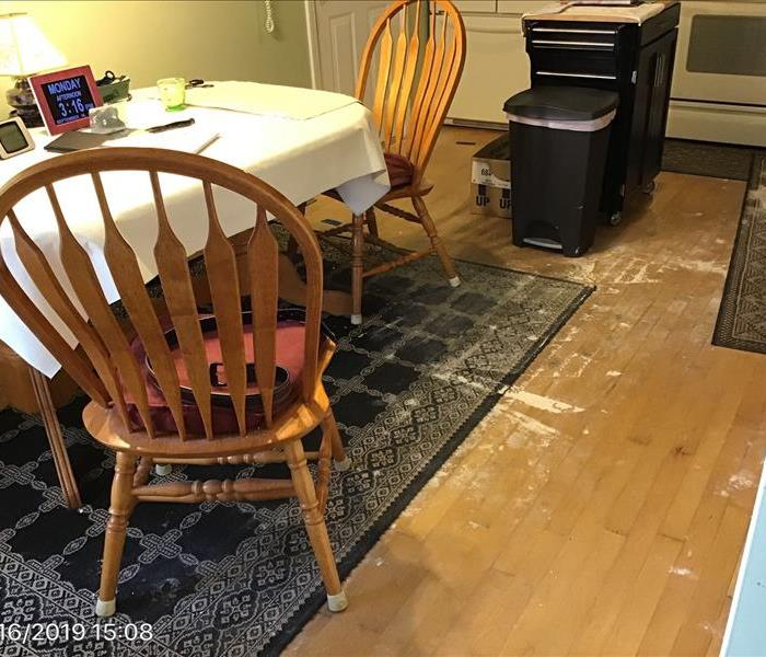 water damaged kitchen with buckled wood floor and sagging ceiling.